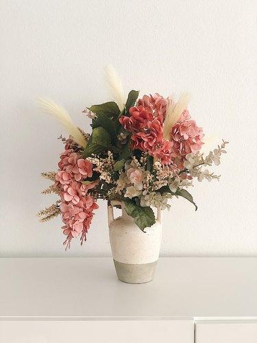 Faux flowers in a rustic vase