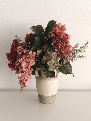 Faux flowers in a rustic vase.