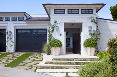 Farmhouse garage doors in black chevron design and white brick exterior
