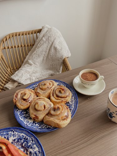 cinnamon rolls and warm drinks on table