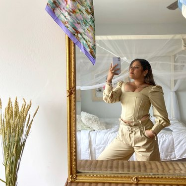 person standing in front of mirror with bed in background