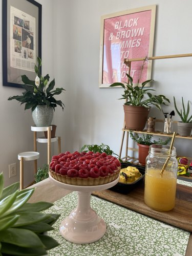 pie on stand with decor and plants in background
