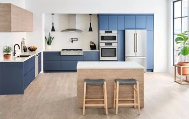 induction stove in Kitchen with blue cabinets, light wood kitchen island with light wood barstools, light wood floors, stainless steel appliances.
