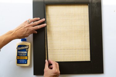 Attaching black trim pieces to black and cane cabinet panel