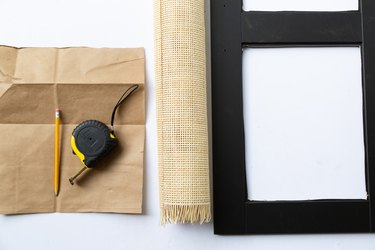 Brown paper with pencil and measuring tape, next to caning and black IKEA cabinet