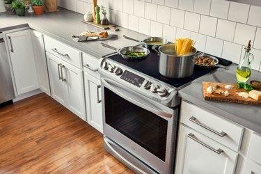 Induction stove, white cabinets, white tile backsplash.
