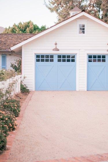 light blue garage door on white house exterior