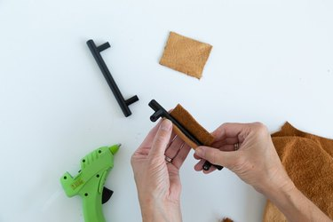 Attaching leather scraps to black cabinet handles