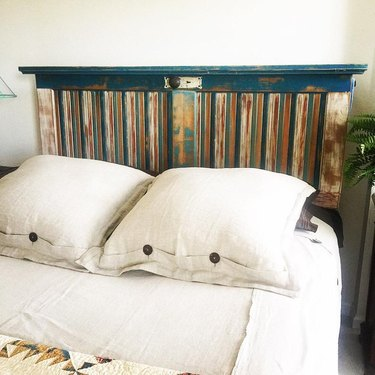 Multicolor louvered door as headboard with white beddings