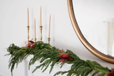 Holiday mantel garland decorated with berry-colored dried floral sprays