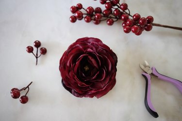 Faux ranunculus and berries clipped off their stems