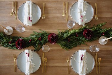 Holiday dinner table setting with pine garland and berry toned flowers and berries