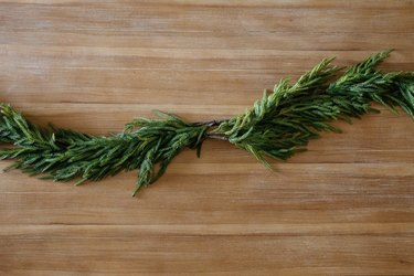 Two pine garlands arranged in center of wood table