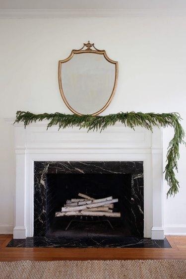 Pine garland arranged asymmetrically on fireplace mantel