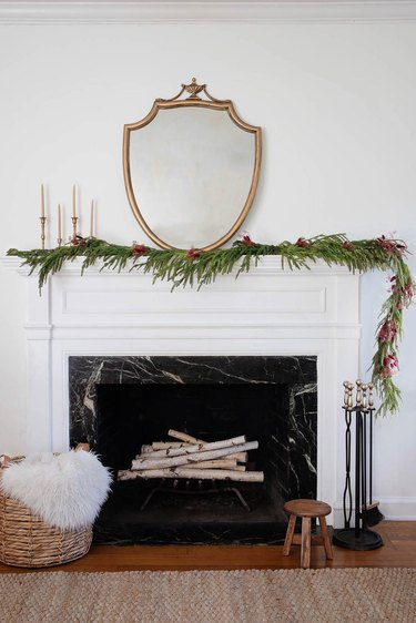 Asymmetrical mantel garland decorated with berry-colored dried floral sprays