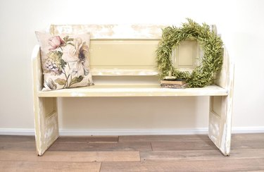Cream and beige hallway bench made of vintage doors with pillow and wreath on seat
