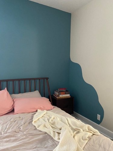 bed with neutral bedding and pink pillows near wavy accent wall