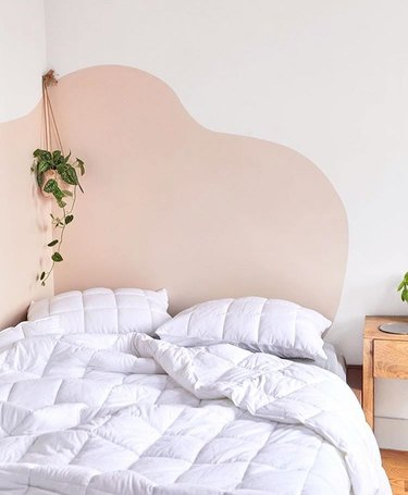 bedroom with white bedding and a wavy accent wall