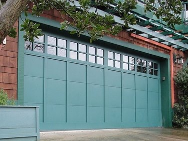 blue-green garage door on wood shingle house