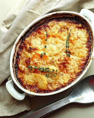 Grandbaby Cakes Potato and Squash Gratin in casserole dish with herbs on top