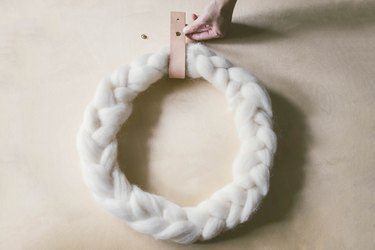 Attaching leather strip around braided wool wreath with brass Chicago screw