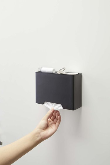 person grabbing mask from dispenser