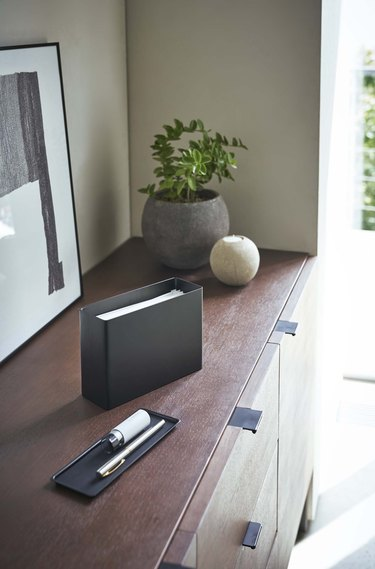 face mask dispenser on wooden furniture with plants nearby