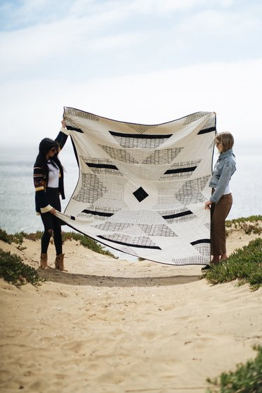 two people holding a large quilt outside
