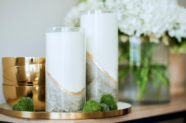 two concrete candles near flowers