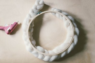 Hot gluing braided wool around wood embroidery hoop