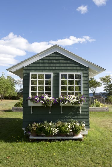 Cute shed with windows and flower boxes against a perfect blue sky with a few puffy clouds
