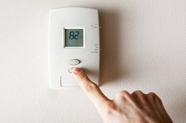 A woman is pressing the down button of a wall attached house thermostat with digital display showing the temperature