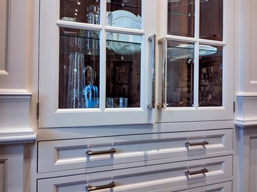glass built-in display cabinet in a kitchen, displaying fine china dishes and crystal pitchers