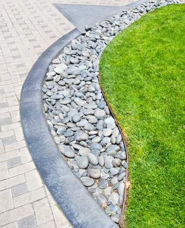 River rock stone border against fresh grass and paving bricks