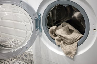 Towel hanging out of a washing machine