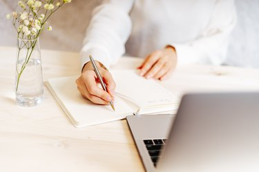 Woman writes in notebook on desk with laptop