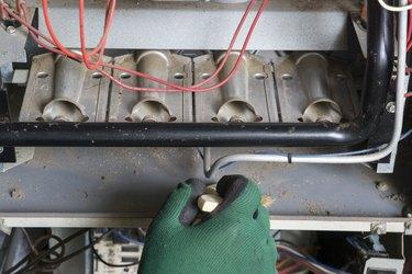 Technician Cleaning A Natural Gas Furnance