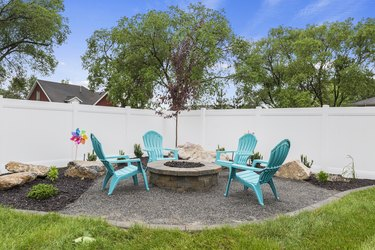 Four plastic turquoise chairs surrounding neat fire pit