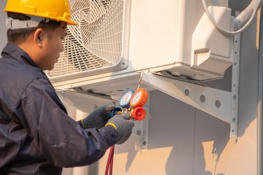 Technician use measuring equipment for filling air conditioners.