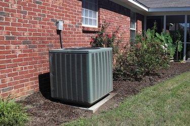Home HVAC Unit next to modern brick home.