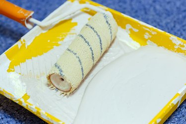 Paint roller in a yellow tray with white paint