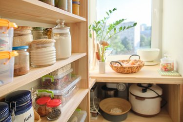 Wooden shelves with food and utensils, kitchen appliances in the pantry