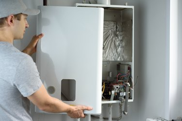 A man checks a gas boiler for home heating. Maintenance and repair of gas heating
