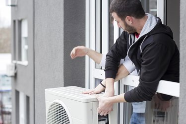 Young man installing air conditioner in an apartment