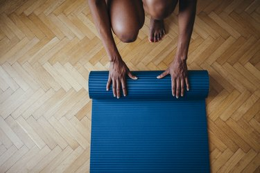 An Anonymous Fitness Woman Folding Blue Exercise Mat