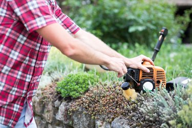 Close-up of a young man starting a string trimmer