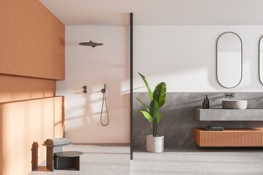 Interior of modern bathroom with white and wooden walls, concrete floor, double sink with two mirrors above it and shower cabin.
