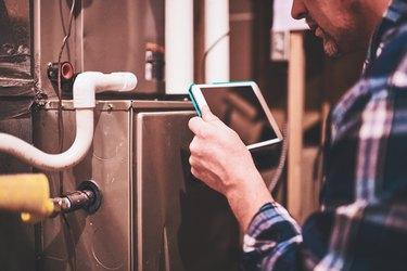 Home Appraiser or Home Inspector using digital tablet in furnace room