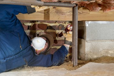Home inspector examines a freeze protected crawl space water line.