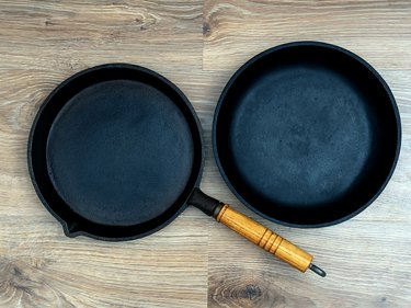 Two cast-iron skillets, one with a wooden handle, on a wood or laminate surface